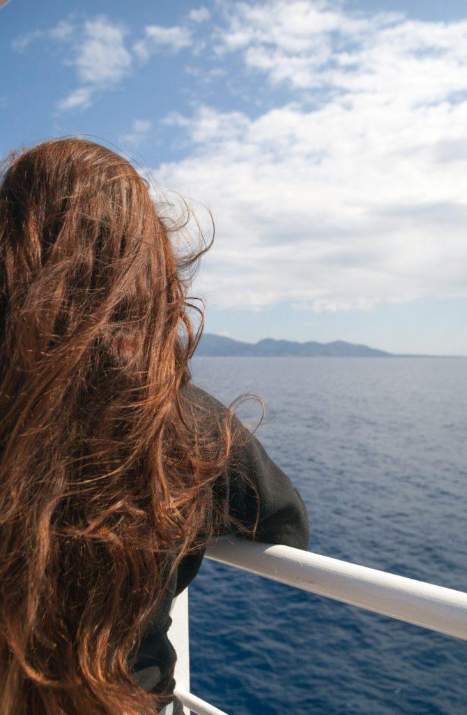 Passenger of cruise ship looking at sea and island